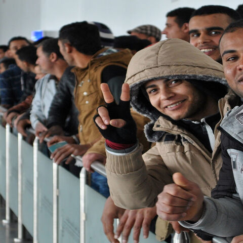 Egyptians, who were formerly residing in Libya, flash the sign for victory as they line up for checks by Tunisian customs at Djerba airport on the Tunisian-Libyan border, before being evacuated on a flight heading to Cairo, Egypt, Feb. 23, 2015.