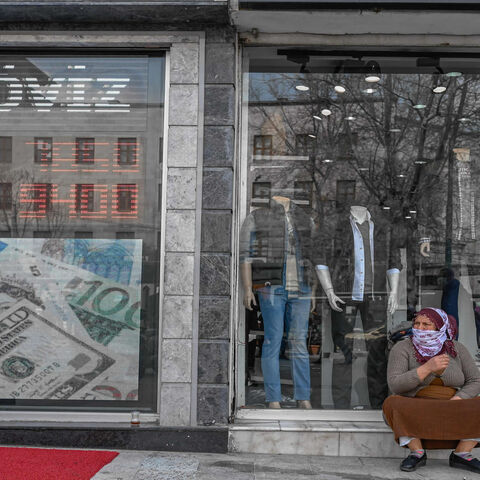 Women sit next to an exchange office at Laleli in Istanbul, Turkey, March 22, 2021.