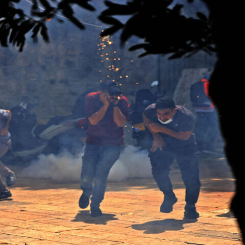 Palestinians run for cover from tear gas fired by Israeli security forces in the Old City, ahead of a planned march to commemorate Israel's takeover of Jerusalem in the 1967 Six-Day War, Jerusalem, May 10, 2021.