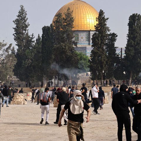 Palestinians run for cover from tear gas fired by Israeli security forces at Jerusalem's Al-Aqsa mosque compound on May 10, 2021, ahead of a planned march to commemorate Israel's takeover of Jerusalem in the 1967 Six-Day War.