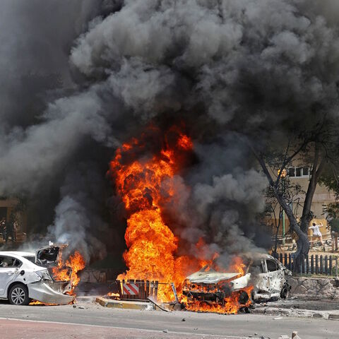 Vehicles are pictured ablaze after a rocket launched from the Gaza Strip, controlled by the Palestinian Hamas movement, landed in the southern Israeli city of Ashkelon on May 11, 2021.