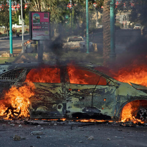 An Israeli police car burns after an Arab Israeli demonstration following the funeral of Mousa Hassouna in the central city of Lod, near Tel Aviv, Israel, May 11, 2021.