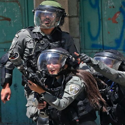 A member of the Israeli security forces fires tear gas at Palestinian protesters, during confrontations with them in the occupied West Bank city of Hebron, on May 14, 2021.