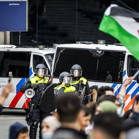 Riot police officers stand in front of demonstrators during a protest in support of Palestine on Jaarbeursplein in Utrecht, on May 14, 2021.