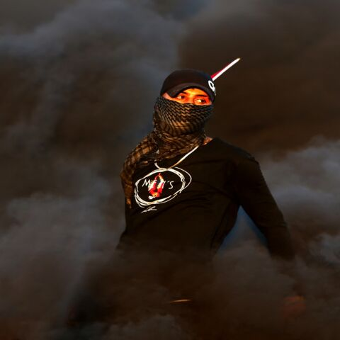 A Palestinian demonstrator stands amidst smoke from burning tires during a protest against the tension in Jerusalem and the Israeli-Gaza fighting, on May 17, 2021, in the occupied West Bank, near the settlement of Beit El next to Ramallah.