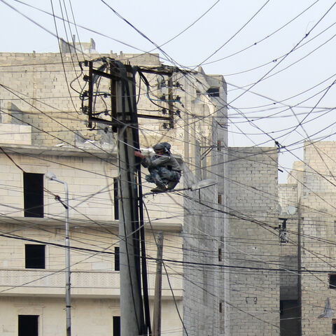 A man tries to fix electrical wires in the Salahuddin neighborhood, Aleppo, Syria, Jan. 27, 2014.