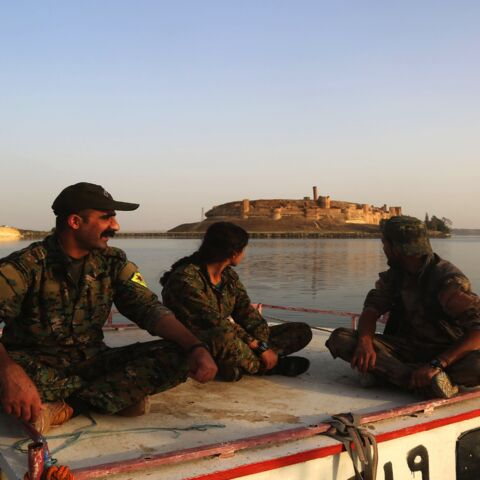 Members of the US-backed Syrian Democratic Forces (SDF), made up of an alliance of Arab and Kurdish fighters, look toward the Jaabar Castle as they sit on a boat at Lake Assad, an enormous reservoir created by the Tabqa dam, on April 29, 2017.