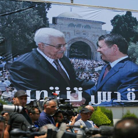 A photo montage of Jordan's King Abdullah (R) and Palestinian President Mahmoud Abbas shaking hands in front of Al-Aqsa Mosque compound is seen on a building during a welcome ceremony of the Jordanian king in Ramallah, West Bank, Aug. 7, 2017.
