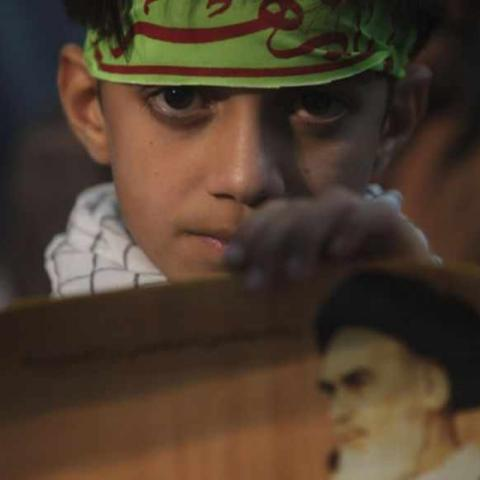 A youth holds a picture of Iran's late leader Ayatollah Ruhollah Khomeini during a ceremony to mark Khomeini's death anniversary at his tomb at Tehran's Behesht-Zahra cemetery June 3, 2011. REUTERS/Morteza Nikoubazl (IRAN - Tags: POLITICS ANNIVERSARY RELIGION) - RTR2N9KQ