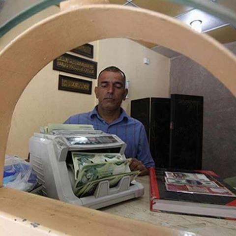 A man counts wads of Iraqi dinars using a money counting machine at a currency exchange shop in Baghdad October 1, 2012. Many Iraqis have lost faith in their dinar currency but to some foreign speculators, it promises big profits. The contrast underlines the uncertainties of investing in Iraq as the country recovers from years of war and economic sanctions. Picture taken October 1, 2012. To match IRAQ-ECONOMY/DINAR  REUTERS/Saad Shalash (IRAQ - Tags: BUSINESS POLITICS) - RTR38QU3