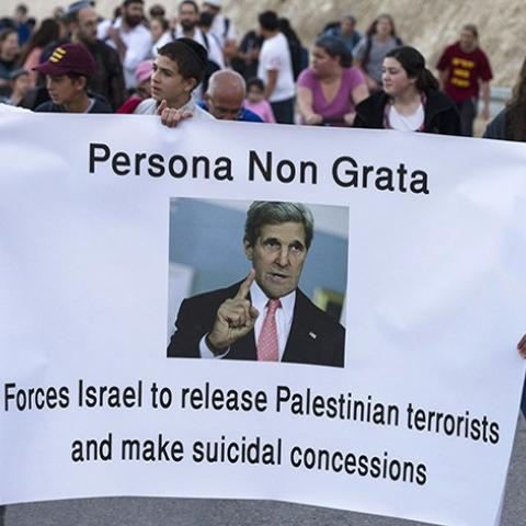 Right-wing Israelis hold a banner depicting U.S Secretary of State John Kerry as they march during a rally in E1, an area in the West Bank near Jerusalem February 13, 2014. Thousands of right-wing Israelis took part in the rally on Thursday in E1, a geographically sensitive area which connects the two parts of the Israeli-occupied West Bank outside Arab suburbs of East Jerusalem, calling for Israeli building in the area which Palestinians seek for a contiguous future state. REUTERS/Baz Ratner (WEST BANK - T