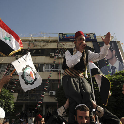 Supporters of Syria's President Bashar al-Assad wave the national flags and chant slogans in front of General Federation of Trade Unions building, during presidential election in Damascus June 3, 2014. Syrians began voting on Tuesday in an election expected to deliver an overwhelming victory to President Bashar al-Assad in the midst of a civil war that has fractured the country and killed more than 160,000 people. REUTERS/ Omar Sanadiki  (SYRIA - Tags: CIVIL UNREST POLITICS ELECTIONS) - RTR3RXFT