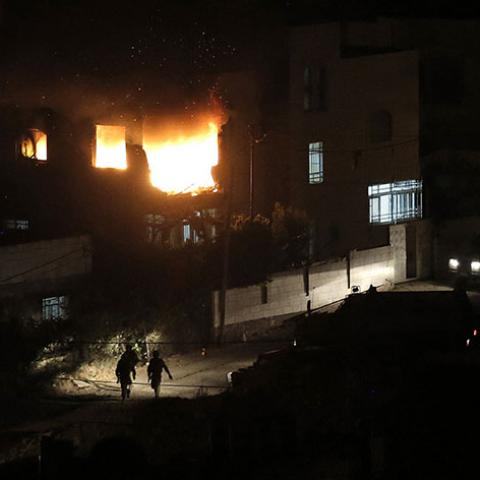 Israeli soldiers walk as flames are seen at the family home of an alleged abductor after a blast on the top floor in the West Bank City of Hebron July 1, 2014. The bodies of three missing Israeli teenagers were found in the occupied West Bank, and Israel vowed to punish Hamas, the Palestinian group it accuses of abducting and killing them. Troops set off explosions in the family homes of the alleged abductors, blowing open a doorway in one, an army spokeswoman said, while television footage showed the other