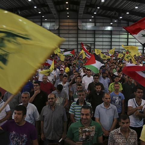"Hezbollah supporters wave Lebanese, Syrian, Palestinian and Hezbollah flags as they listen to their leader Sayyed Hassan Nasrallah addressing his supporters during a rally to mark ""Quds (Jerusalem) Day"" in Beirut's southern suburbs July 25, 2014. REUTERS/Sharif Karim    (LEBANON - Tags: POLITICS CIVIL UNREST RELIGION) - RTR4056R"