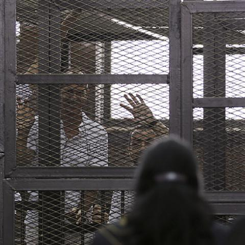 "Al Jazeera journalists (L-R) Mohammed Fahmy, Peter Greste and Baher Mohamed wave to a friend and Fahmy's fiancee as they stand behind bars in a court in Cairo June 1, 2014. The trial of the three Al Jazeera journalists accused of aiding of a ""terrorist organisation"" has been postponed to June 6. The Qatar-based television network's journalists - Peter Greste, an Australian, Mohamed Fahmy, a Canadian-Egyptian national, and Baher Mohamed, an Egyptian - were detained in Cairo on December 29. All three have den"