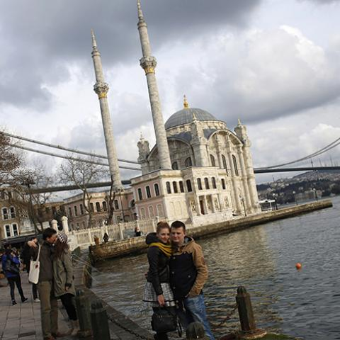 Couples pose for souvenir pictures in front of the Ottoman-era Ortakoy Mecidiye mosque by the Bosphorus strait in Istanbul January 5, 2015.  REUTERS/Murad Sezer (TURKEY - Tags: RELIGION CITYSCAPE TRAVEL SOCIETY) - RTR4K534