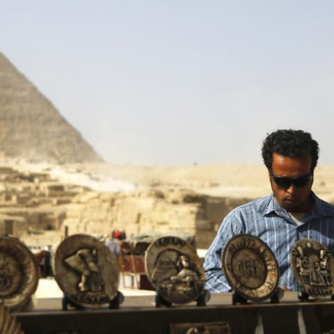 A souvenirs vendor waits for tourists in front of the Sphinx and the Giza Pyramids on the outskirts of Cairo, December 9, 2014.  Egypt's tourism revenues jumped 112 percent to about $2 billion in the third quarter of 2014, a tourism ministry official said, suggesting the key industry was showing signs of recovery, albeit from a particularly bad third quarter last year. Tourism, an important source of foreign currency, has been hammered since the popular uprising that toppled Hosni Mubarak in 2011.   REUTERS
