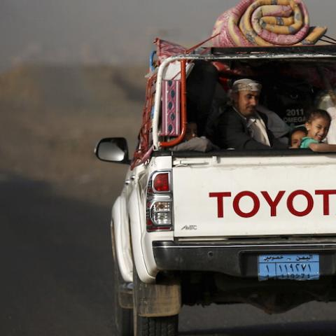A man and his children ride on the back of a pick-up truck with their luggage as they flee Saudi-led air strikes in Sanaa April 6, 2015. Foreign nationals were on their way out of Yemen on Monday (April 6) as 12 days of strikes by a Saudi-led coalition have failed to halt the advance of the Iran-allied Houthis and triggered a growing humanitarian crisis for residents in central districts now cut off from the mainland. REUTERS/Khaled Abdullah - RTR4W8WJ