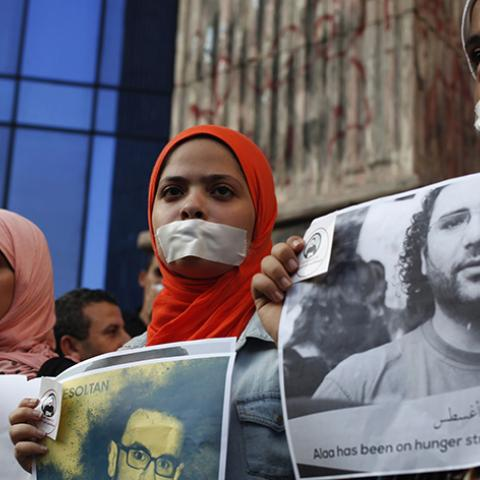 Protesters hold pictures during a protest in support of imprisoned activists who are in a hunger strike at prison, in front of the Press Syndicate, in Cairo August 25, 2014. REUTERS/Asmaa Waguih (EGYPT - Tags: POLITICS CIVIL UNREST MEDIA) - RTR43OK4