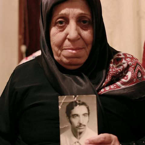 Fatima Rida holds a photo of her Missing Husband, Hussein Moalim who disappeared during Lebanon's civil war in March 1976.