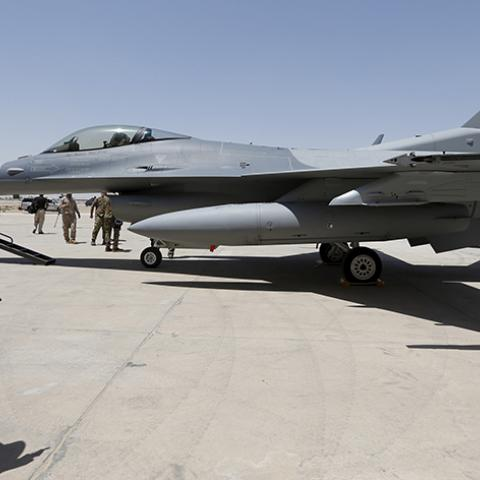 An Iraqi solider stands guard near a F-16 fighter jet during an official ceremony to receive four of these aircrafts from the U.S., at a military base in Balad, Iraq, July 20, 2015. REUTERS/Thaier Al-Sudani - RTX1L2B2