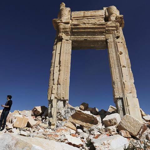 "A journalist stands at the remains of the Temple of Bel in the historic city of Palmyra, in Homs Governorate, Syria April 1, 2016. REUTERS/Omar Sanadiki  SEARCH ""PALMYRA SANADIKI"" FOR THIS STORY. SEARCH ""THE WIDER IMAGE"" FOR ALL STORIES - RTSD71B"