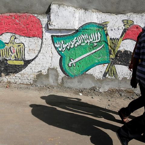 Men walk are in front of graffiti depicting relations between Egypt and Saudi Arabia in Cairo, Egypt, October 12, 2016. Picture taken October 12, 2016. REUTERS/Amr Abdallah Dalsh - RTSS9QT