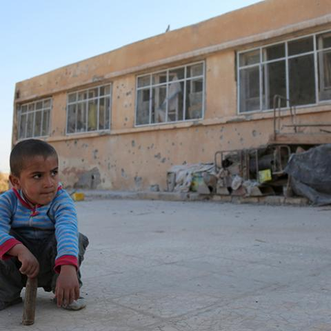 An internally displaced boy sits on the ground near a school in the village of al-Heesha in Raqqa district after it was captured from Islamic State, north of Raqqa city, Syria November 15, 2016. REUTERS/Rodi Said - RTX2TU3Q