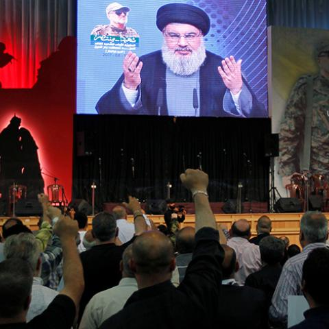 Hezbollah leader Sayyed Hassan Nasrallah addresses his supporters from a screen, during a ceremony marking a year after Hezbollah commander Mustafa Badreddine(picture on banner) was killed in an attack in Syria, in Beirut's southern suburbs, Lebanon May 11, 2017. REUTERS/Aziz Taher - RTS16886