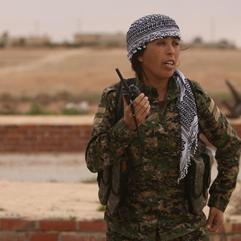 Rojda Felat, commander of a U.S.-backed operation by Kurdish and Arab fighters to capture the Syrian city of Raqqa, uses her walkie talkie near the Taqba Dam, west of Raqqa, Syria March 30, 2017. Picture taken March 30, 2017. To match Interview MIDEAST-CRISIS/SYRIA-RAQQA REUTERS/Rodi Said - RTX33I1G