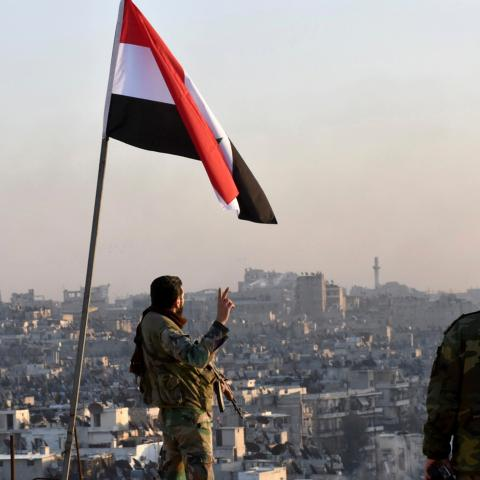 A Syrian government soldier gestures a v-sign under the Syrian national flag near a general view of eastern Aleppo after they took control of al-Sakhour neigbourhood in Aleppo, Syria in this handout picture provided by SANA on November 28, 2016. SANA/Handout via REUTERS ATTENTION EDITORS - THIS IMAGE WAS PROVIDED BY A THIRD PARTY. EDITORIAL USE ONLY. REUTERS IS UNABLE TO INDEPENDENTLY VERIFY THIS IMAGE. - RC14B3B13650