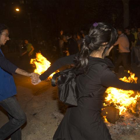 "A woman dances with men during the ""Chaharshanbeh Soori"" festival in Tehran March 18, 2008. People jump over fire during the festival to burn away the year's sins on the last Tuesday night before the new year. REUTERS/Raheb Homavandi (IRAN) - GM1E43J07KQ01"
