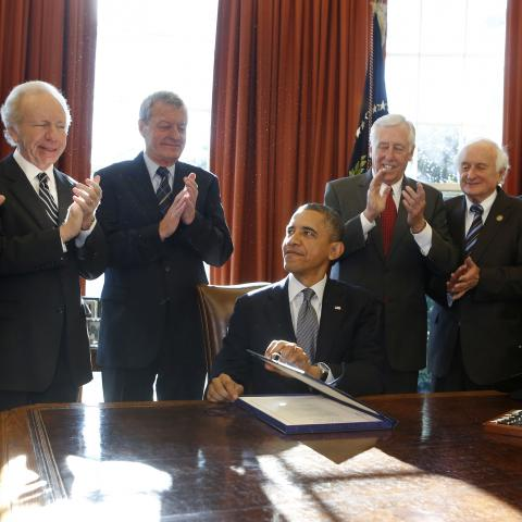 U.S. President Barack Obama (seated) signs H.R. 6156, the Russia and Moldova Jackson-Vanik Repeal and Magnitsky Rule of Law Accountability Act, in the Oval Office of the White House in Washington, December 14, 2012. From L-R are: U.S. Sen. Ben Cardin, U.S. Sen. Joe Lieberman, U.S. Sen. Max Baucus, Obama, U.S. Rep. Steny Hoyer, U.S. Rep. Sandy Levin, U.S. Rep. Jim McGovern, and U.S. Rep. Gregory Meeks.      REUTERS/Larry Downing  (UNITED STATES - Tags: POLITICS) - GM1E8CF053K01