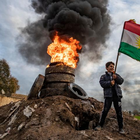 A boy stands holding a Kurdish flag near a bonfire marking the Kurdish holiday of Noruz in Qamishli in Syria's northeastern Hasakah province on March 20, 2020, after the local authorities cancelled holiday celebrations due to fears of the spread of COVID-19 coronavirus disease. - The Persian New Year is an ancient Zoroastrian tradition celebrated by Iranians and Kurds which coincides with the vernal (spring) equinox and is calculated by the solar calendar. (Photo by DELIL SOULEIMAN / AFP) (Photo by DELIL SO