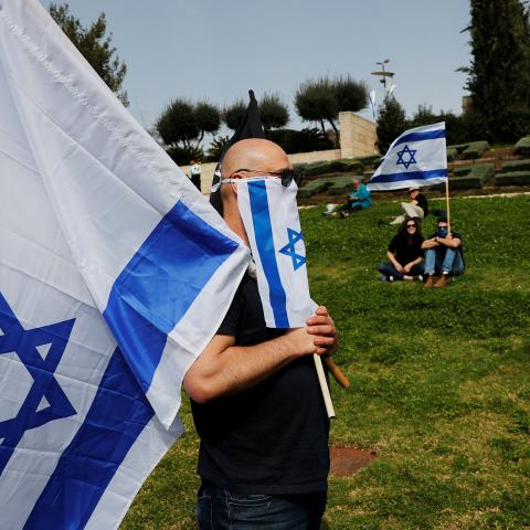 Israelis hold national flags during a demonstration against Prime Minister Benjamin Netanyahu's caretaker government, accusing it of undemocratic measures, outside the parliament in Jerusalem March 23, 2020 REUTERS/Ronen Zvulun - RC2QPF9E73ES