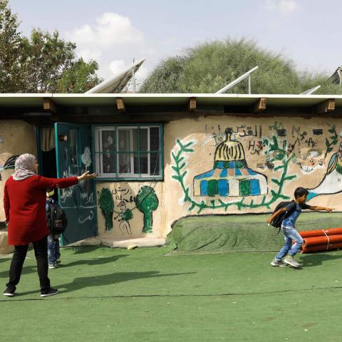 "Palestinian Bedouin schoolchildren play in the yard of their school in the Palestinian Bedouin village of Khan al-Ahmar, east of Jerusalem, in the occupied West Bank, on October 21, 2018. - Israeli Prime Minister Benjamin Netanyahu has frozen plans to demolish a strategically located Bedouin village in the occupied West Bank that has drawn the world's attention, his office said on October 21. ""The intention is to give a chance to the negotiations and the offers we received from different bodies, including i"