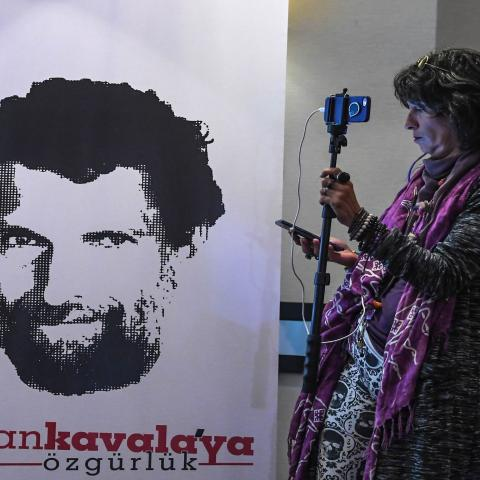 A journalist stands in front of a poster featuring jailed businessman and philanthropist Osman Kavala during a press conference of his lawyers on October 31, 2018. - Osman Kavala was arrested a year ago by Turkish authorities and has still to be charged with an offence. (Photo by OZAN KOSE / AFP)        (Photo credit should read OZAN KOSE/AFP via Getty Images)