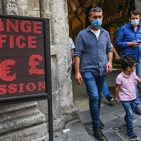 People walk past a screen near a currency exchange agency near Grand bazaar, in Istanbul, on September 24, 2020. - Turkey's central bank on September 24, 2020 raised its main interest for the first time since September 2018, boosting the rate by two percentage points to help the lira recover from historic lows. (Photo by Ozan KOSE / AFP) (Photo by OZAN KOSE/AFP via Getty Images)