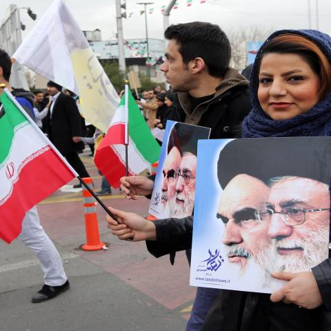 Iranians hold their national flag and posters bearing portraits of Supreme Leader, Ayatollah Ali Khamenei (R) and the founder of Iran's Islamic Republic, Ayatollah Ruhollah Khomeini (L) during a rally in Tehran's Azadi Square (Freedom Square) to mark the 36th anniversary of the Islamic revolution on February 11, 2015. Iranians gathered in cities and villages all over the country to mark the 36th anniversary of the revolution which transformed the country from a US-backed monarchy into a cleric-ruled republi