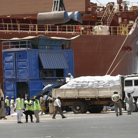 Sudanese dockers unload bags of sorgham (cereal) from one of two US ships carrying humanitarian aid supplies provided by the US development agency USAID, at Port Sudan on the red sea coast on June 5, 2018. - The United States is the largest single donor to the world food program in Sudan and regularly distributes food aid to the East African country. This shipment will be distributed to over a  million Sudanese who are in need of assistance. (Photo by ASHRAF SHAZLY / AFP)        (Photo credit should read AS